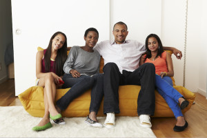 Mixed-race family at home on sofa